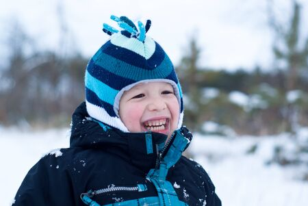 Happy boy in blue clothes in snowing winter outdoor photo
