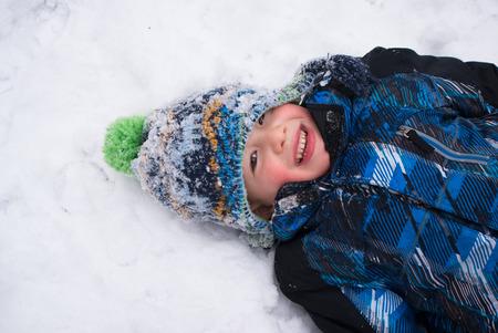 jungle boy: Cheerful boy playing in snow angel