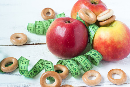 baranka: Apples, barankas and centimeter on white wooden table. concept of dietary food