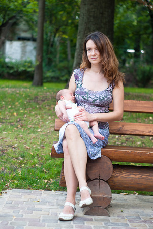 mother on bench: Mother and her newborn son on a park bench