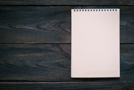 hoja en blanco: Cuaderno con la hoja en blanco sobre una superficie de madera. Vista superior. Teñido de imagen