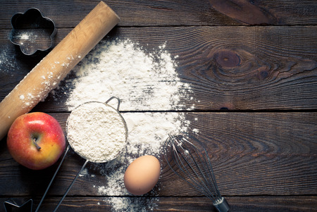 eggs: Ingredients for cooking baking - flour, egg, cookie cutters on wooden table. Image tinting.