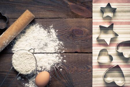 tinting: Ingredients for cooking baking - flour, egg, cookie cutters on wooden table. Image tinting.