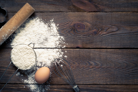Ingredients for cooking baking - flour, egg, cookie cutters on wooden table. Image tinting.