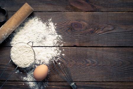 harina: Ingredientes para cocinar hornear - harina, huevo, cortadores de galletas en la mesa de madera. Image tintado.