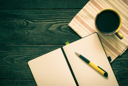 tinting: Notebook and a cup of coffee on the table. Image tinting