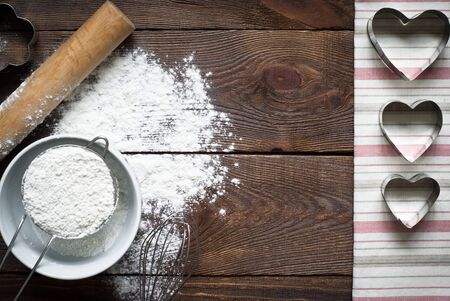 cosiness: Ingredients for cooking baking and cookie cutters on wooden table
