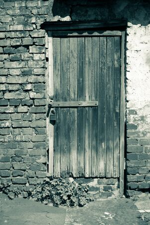 reside: Old wooden door - entrance to the poor house. Monochrome image in retro style Stock Photo