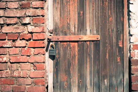 reside: old shabby wooden door with a padlock
