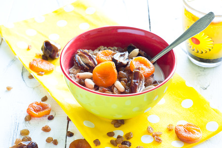 Oatmeal with dried fruit and cup of tea. A fresh and healthy breakfast photo