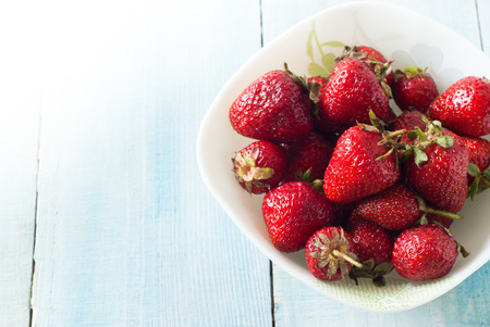 flavorful: Fresh flavorful strawberries in a bowl on a wooden table. Selective focus.