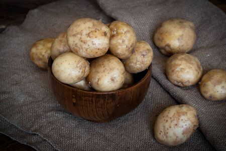 bawl: Raw potatoes in a wooden bowl on sacking