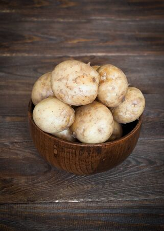 bawl: Raw potatoes in a wooden bowl at the table