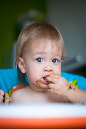 smeared: Child eats cake in the highchair. His face and hands smeared with cake Stock Photo