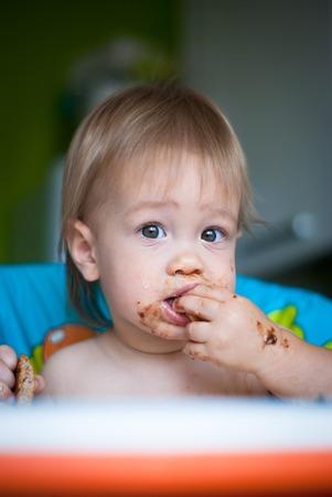 eat smeared baby: El ni�o come la torta en la trona. Su cara y las manos manchadas con la torta Foto de archivo