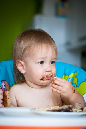 eat smeared baby: Child eats cake in the highchair. His face and hands smeared with cake Stock Photo