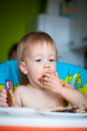 smeared baby: Child eats cake in the highchair. His face and hands smeared with cake Stock Photo