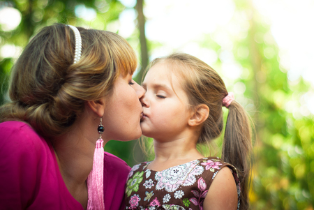 Mother and daughter together in the park kiss each other