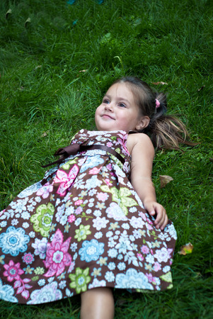 colorful dress: Happy girl in a colorful dress lying in the grass