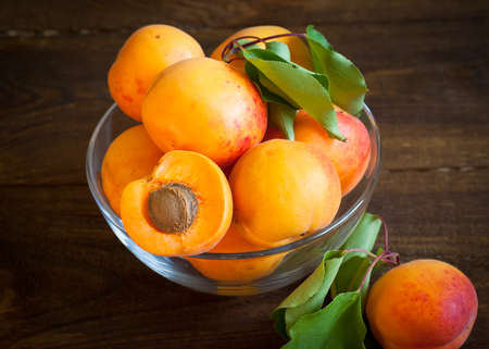 bawl: Some ripe apricots in a glass bowl on a wooden table Selective fokus. Stock Photo