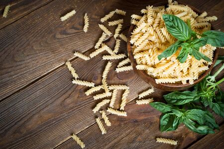 bawl: Uncooked fusilli in the wooden bawl at the table
