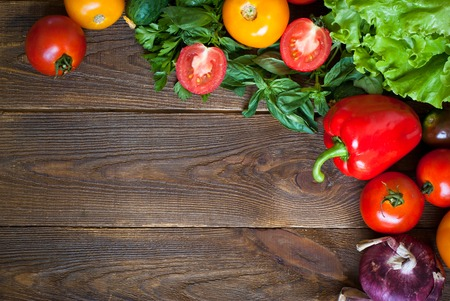 gherkin: Fresh vegetables - tomatoes, pepper and greens at dark wooden table. Stock Photo