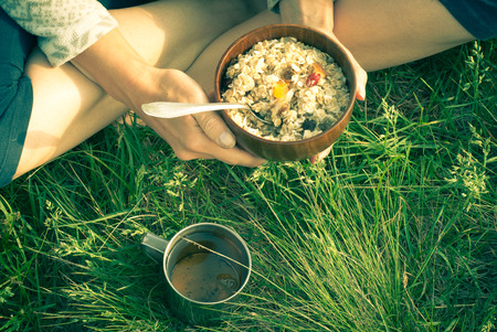 air dried: Morning breakfast open air - oatmeal with dried fruit and a cup of tea Stock Photo