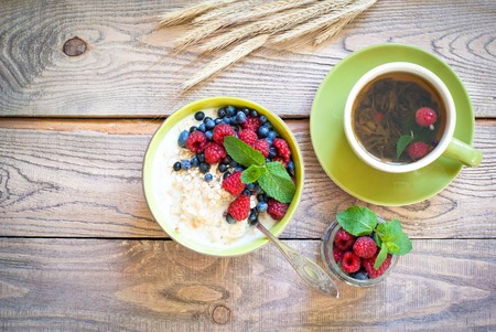 tea light: Healthy breakfast - oatmeal with berries and a cup of green tea