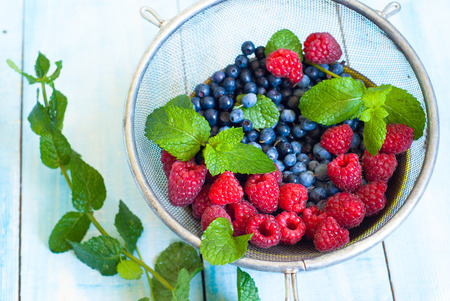 sieve: Blueberries and strawberries with mint leaves in sieve Stock Photo