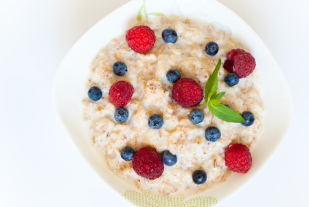 Healthy breakfast - oatmeal with  blueberries and raspberries isolated on white Stock Photo