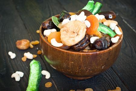 frutos secos: Varias frutas secas en un cuenco de madera - orejones, dátiles, higos y castañas de cajú Foto de archivo