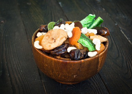dried fruits: Various dried fruits in a wooden bowl - dried apricots, dates, figs and cashews