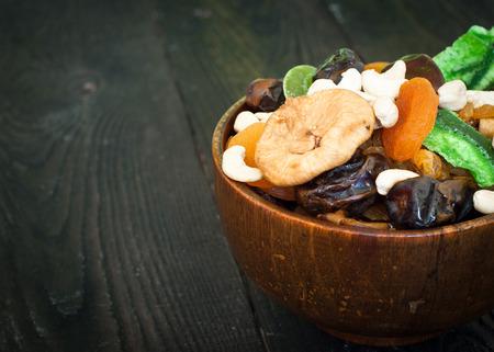 frutas deshidratadas: Varias frutas secas en un cuenco de madera - orejones, dátiles, higos y castañas de cajú Foto de archivo