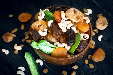 frutas deshidratadas: Varias frutas secas en un cuenco de madera - orejones, d�tiles, higos y casta�as de caj� Foto de archivo
