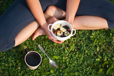 bawl: Healthy breakfast outdoors - oatmeal with fruits and a cup of tea.
