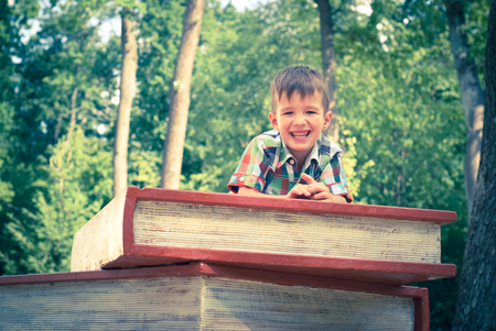 lifestile: A little boy lies on a big stack of books in the park Stock Photo