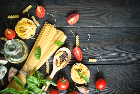 food ingredient: Ingredients for cooking Italian pasta - spaghetti, tomatoes, basil and garlic. Stock Photo