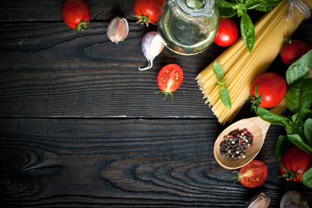 healthy lunch: Ingredients for cooking Italian pasta - spaghetti, tomatoes, basil and garlic. Stock Photo