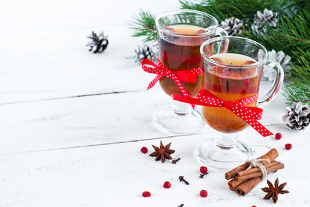 Hot christmas tea with spices - cinnamon, cloves and star anise on a light wooden background