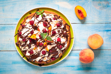frutilla: Summer sponge cake with peaches and raspberries  at blue, top view. Foto de archivo