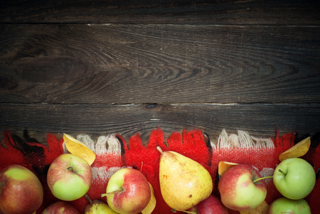 some: Autumn harvest. Apples and pears with yellow leaves on a wooden table.
