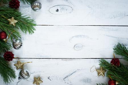クリスマスの背景に木の枝、クリスマスのおもちゃ、コーン。白い木製の表面。トップ ビューのテキストのためのスペース。