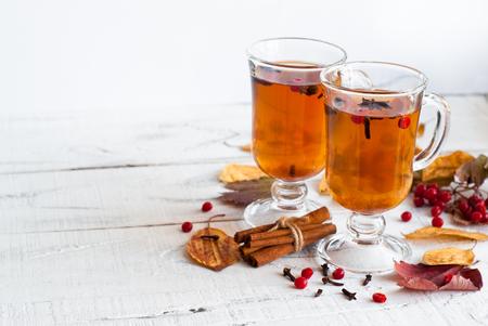 Herfst hete thee met kruiden in glazen beker en vallende bladeren rond.