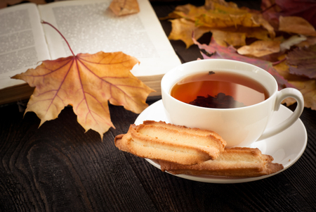autumn food: Autumn hot tea with cookies and falling leaves around.