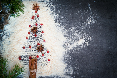 in top: Christmas fir tree made from flour on a dark table.. Top view, copy space.