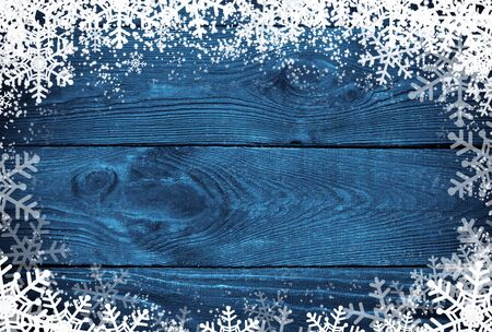 blue christmas: Winter background - snow and snowflakes at navy wooden surface. Stock Photo