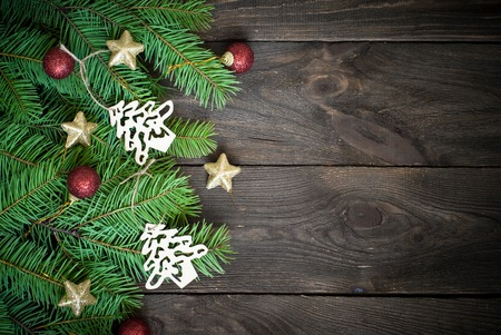 new homes: Christmas background with decorations and spruce branches at dark wooden surface,