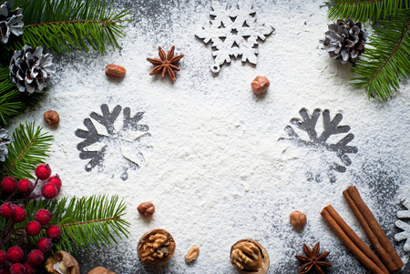 cakes background: Ingredients for christmas baking - flour, spices and cookie cutters.