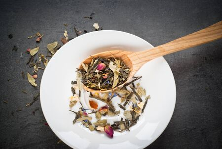 sencha tea: Green Sencha tea flavored with flowers and zest in a wooden spoon on a white saucer