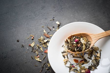 sencha: Green Sencha tea flavored with flowers and zest in a wooden spoon on a white saucer